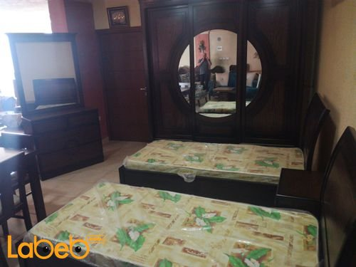 غرفة نوم شباب تشمل سريرين منفصلين بني
