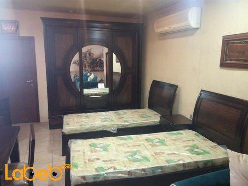 غرفة نوم شباب تشمل سريرين منفصلين خشب لاتية وزان بني
