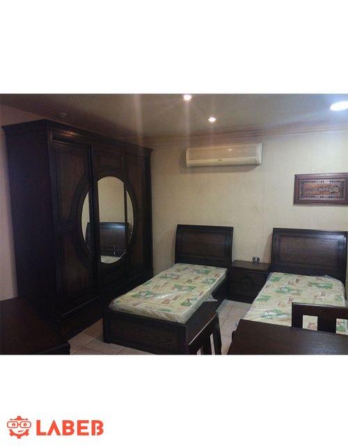 غرفة نوم للشباب تشمل سريرين منفصلين خشب لاتية وزان لون بني