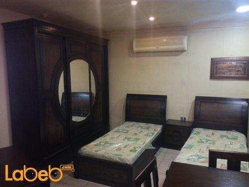 غرفة نوم شباب تشمل سريرين منفصلين خشب لاتية وزان لون بني